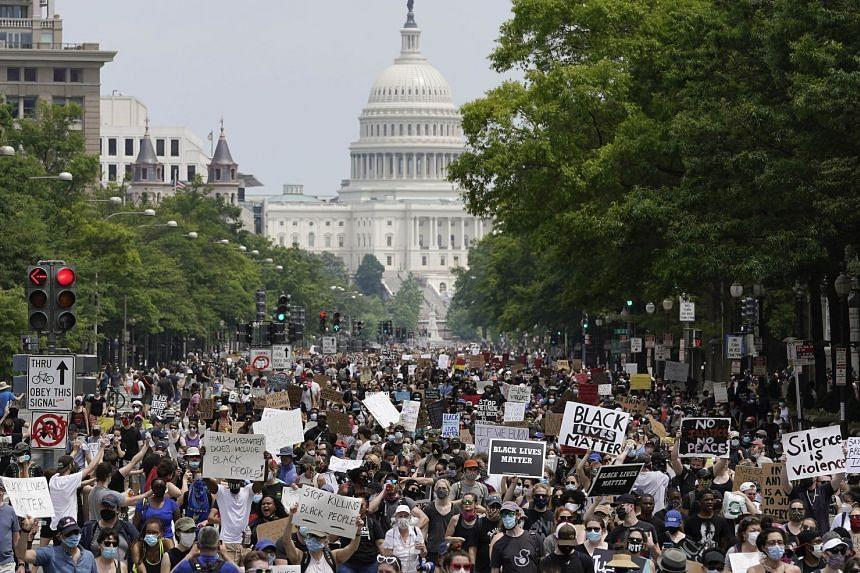 Demonstrators march down Pennsylvania Avenue in Washington, DC.
