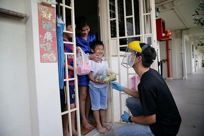 Beneficiaries of The Straits Times School Pocket Money Fund receiving packs of soya products from Mr Bean last month. Prime Minister Lee Hsien Loong pointed to the unity and resilience of Singaporeans as a key ingredient that will help Singapore weat