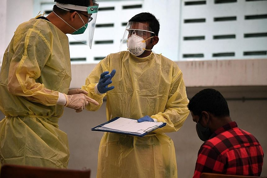 Migrant worker volunteer Rajendran Raja (centre) speaking to a medical worker at Homestay Lodge dormitory last Wednesday. Armed with a clipboard and dressed in full personal protective equipment, he is sometimes mistaken for a Fast (forward assurance