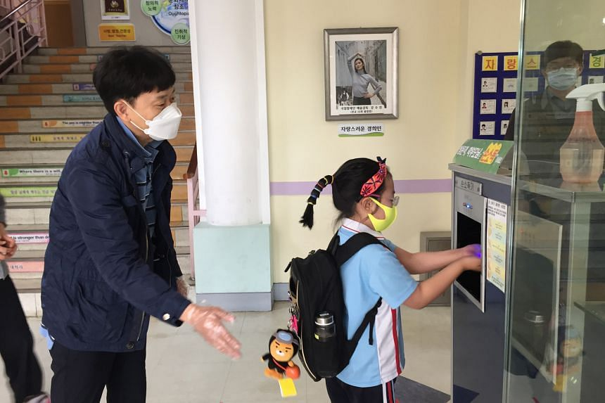 A student at the Affiliated Senior High School of National Taiwan Normal University in Taipei having his temperature taken. ST PHOTO: KATHERINE WEI Pupils at Kyung Hee Elementary School in Seoul have to sanitise their hands before proceeding to their