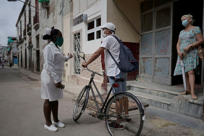 A nurse checks door-to-door for people with symptoms in downtown Havana, Cuba, on June 8, 2020.