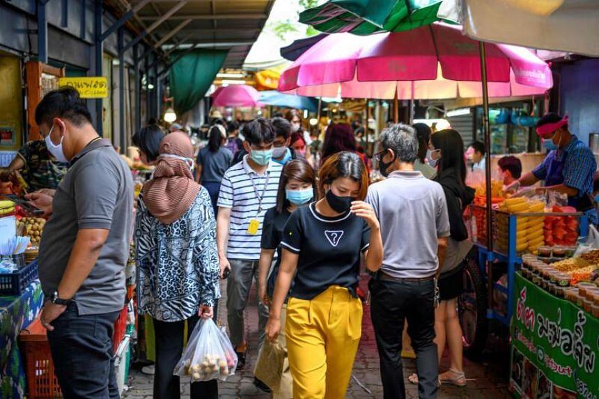 People walking in a street food market in Bangkok, on June 9, 2020.