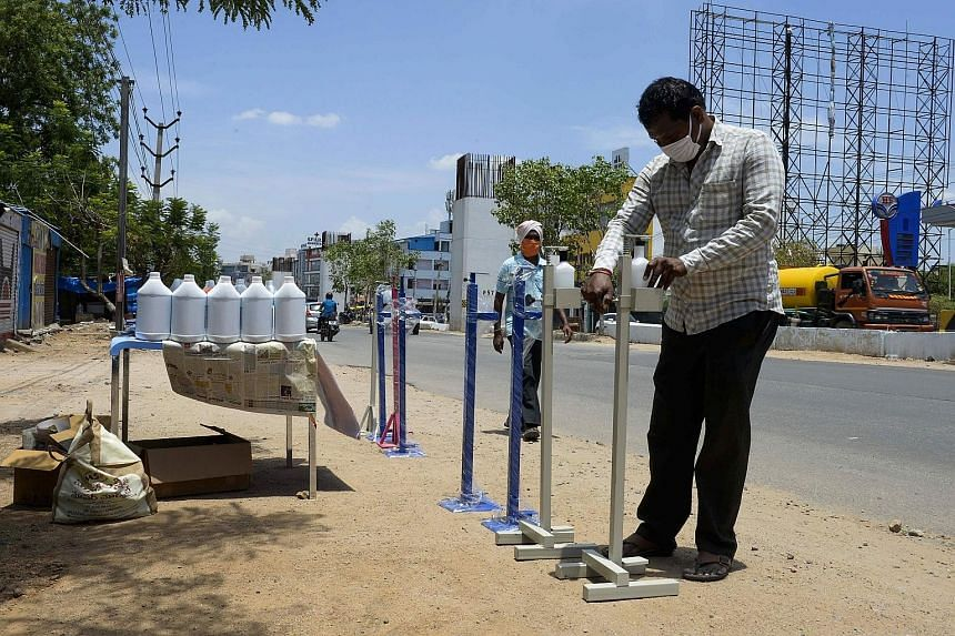 A vendor arranging containers with sanitiser on a street in the south Indian city of Hyderabad yesterday. The country is now easing a partial lockdown to allow millions of people to return to work.