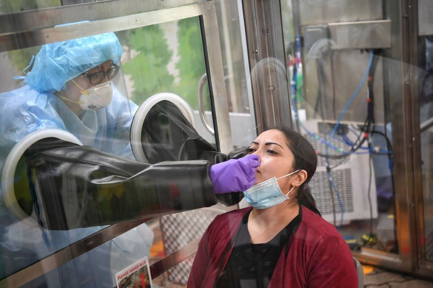 A nurse/swabber places the swab stick into the patient's nose at Gleneagles Hospital on June 5, 2020.