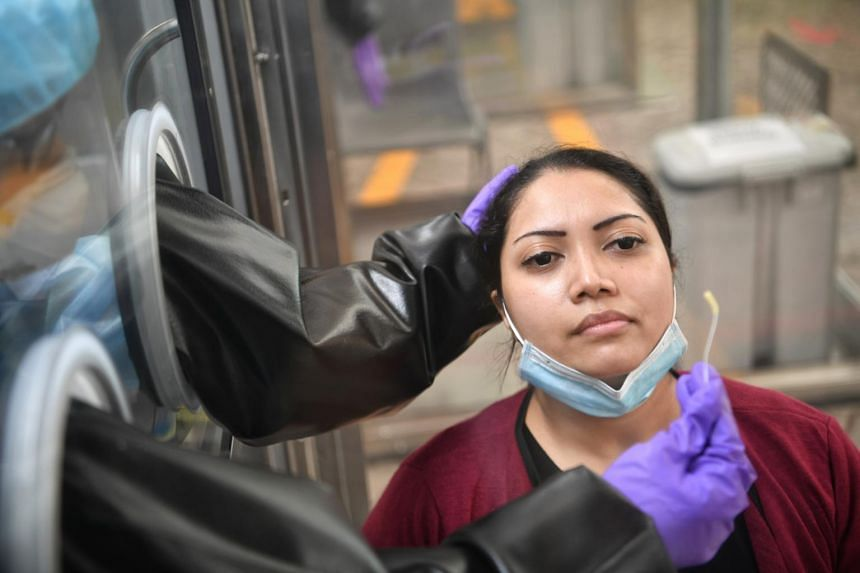 A nurse shows the swab stick to the patient during the mock up swab test at Gleneagles Hospital, on June 5, 2020.