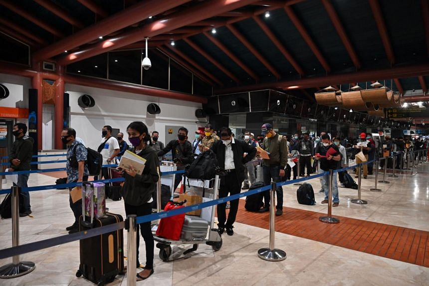 Passengers queue at a checkpoint at Sukarno-Hatta airport in Tangerang, Banten province, on June 4, 2020.