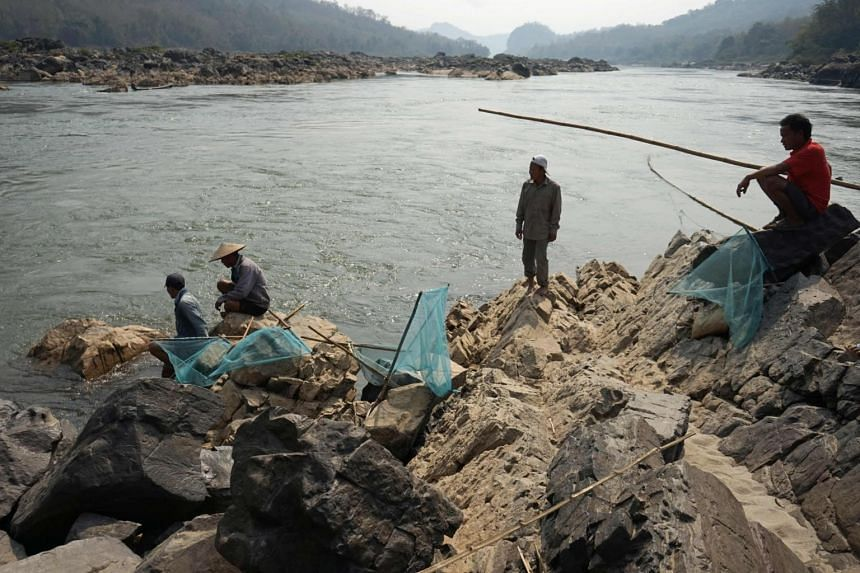 A photo from Feb 8, 2020, shows fishermen laying their nets on the Mekong River close to the site of an approved Laos dam site.