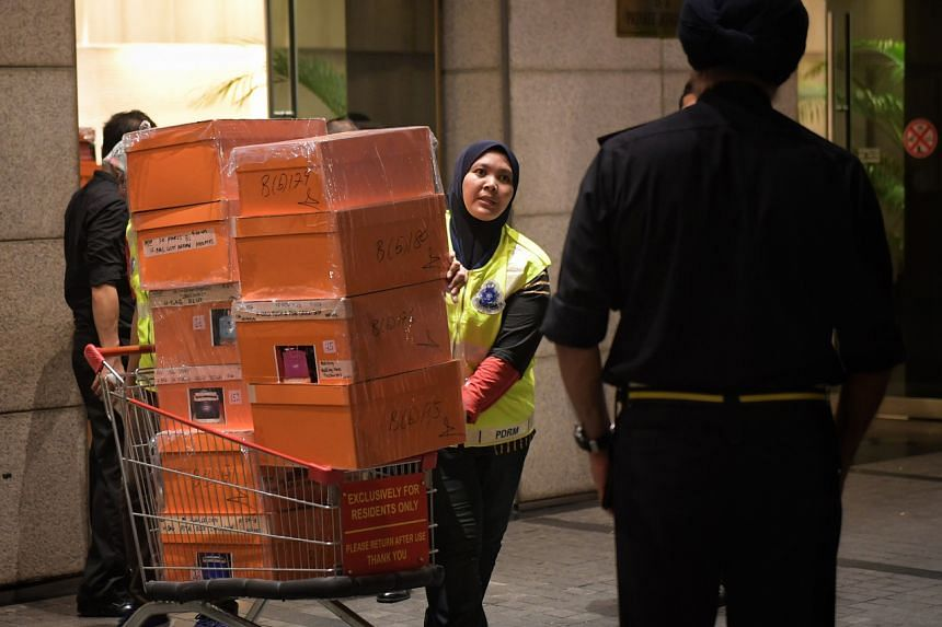 Police carting away boxes containing luxury handbags, jewellery, cash of various denominations, watches and other valuables from a condominium owned by former prime minister Najib Razak's family.