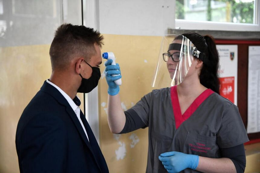 A nursing student checks the body temperature of a secondary school student in Przemysl, Poland, on June 9, 2020.