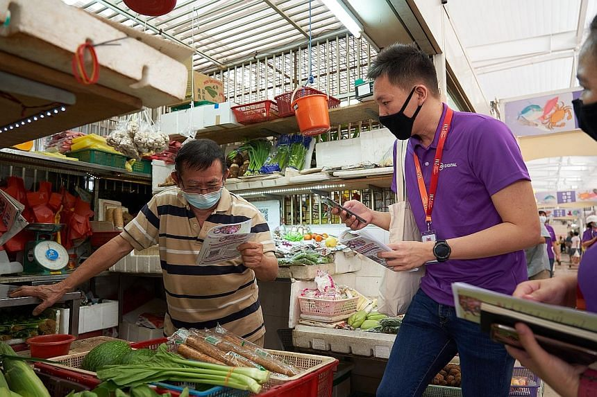 A digital ambassador speaking with a stallholder at Bedok Food Centre and Market on Sunday. By the end of this month, 1,000 such ambassadors will have been recruited to help stallholders learn how to use digital tools.