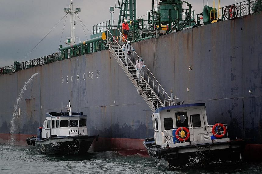 Seafarers disembarking from the STI Carnaby vessel off Marina South Pier yesterday as part of a crew change in Singapore via chartered flights. The Maritime and Port Authority of Singapore has seen a sharp increase in daily crew change applications s