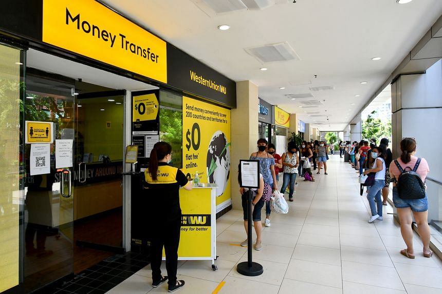 People queueing to remit money at the Western Union branch in Lucky Plaza on May 31, 2020.