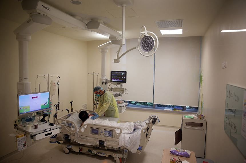 A doctor at Ng Teng Fong General Hospital assists a Covid-19 patient in the isolation room of the intensive care unit on April 21, 2020.