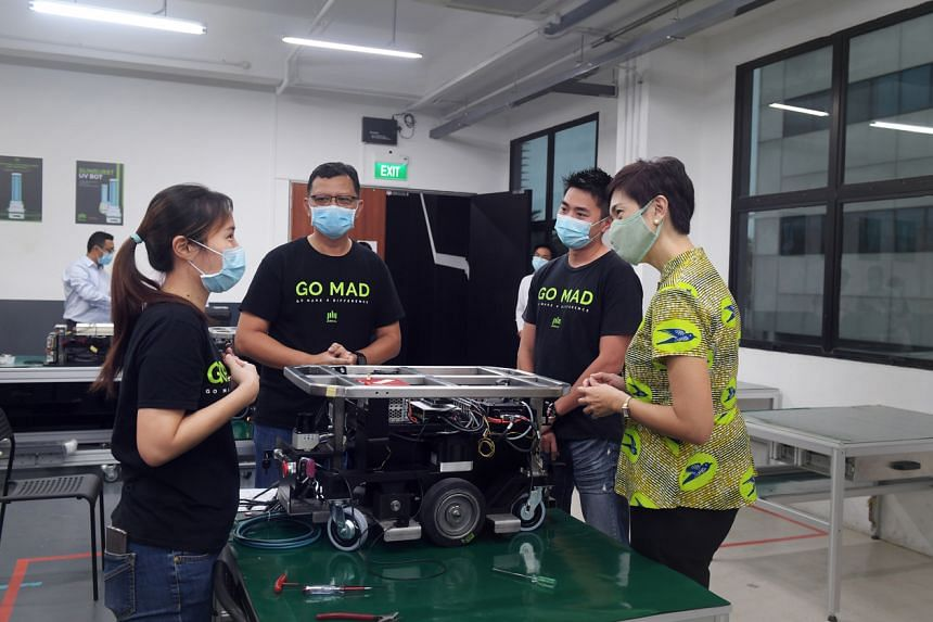 Manpower Minister Josephine Teo speaking to (from left) trainees Rachael Cheah, Solman Erpah and PBA Group chief executive Derrick Yap at the robotics firm.