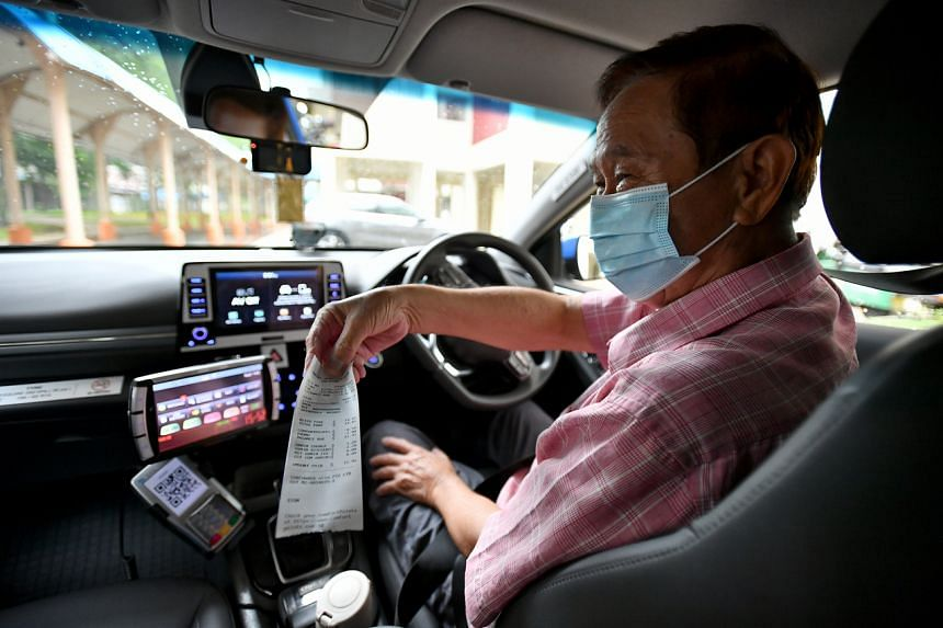Taxi driver Sng Lee Boon issuing a printed receipt for a street-hail trip on June 13, 2020.