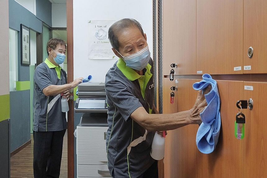 Cleaners Tan Cheng Piew (left), 64, and Pang Tay, 76, at work in an office on Friday. The Covid-19 outbreak has highlighted the plight of essential workers, many of whom continue to go to work often for a low salary, while the rest of Singapore is en