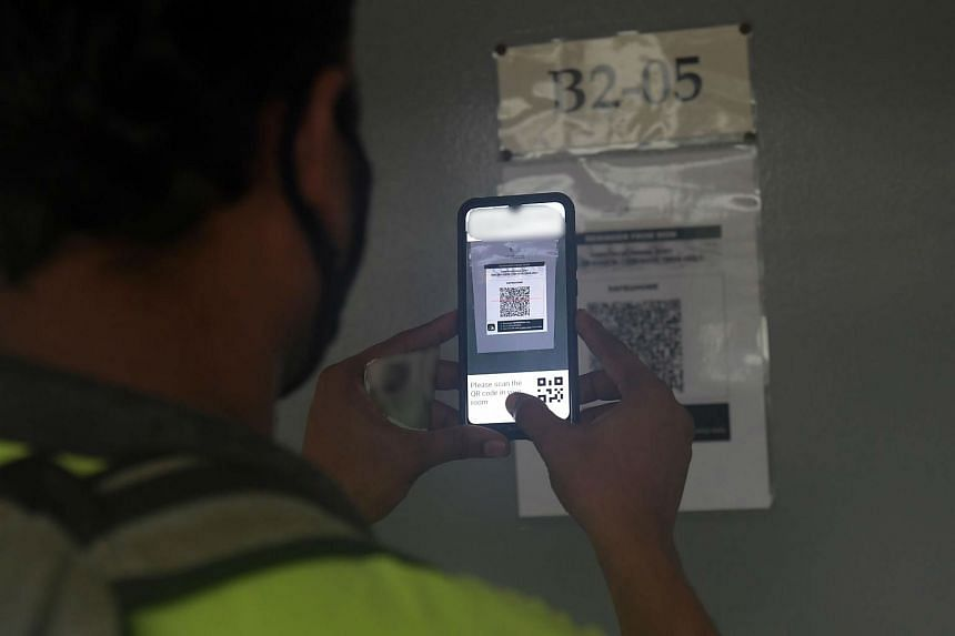 A worker at Central Staff Apartments scanning the QR code on his room door before leaving to go to work.