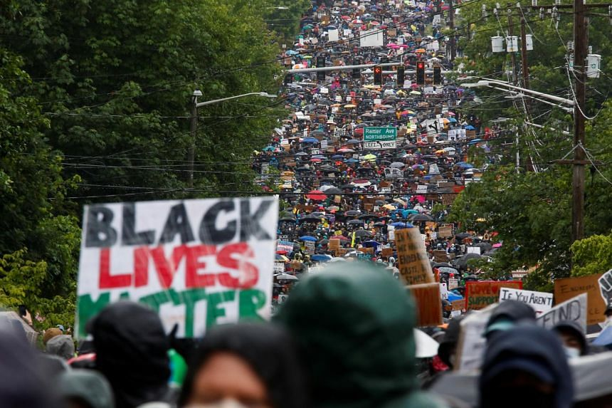 Tens of thousands participate in a silent protest march organised by Black Lives Matter Seattle-King County in Seattle, Washington, US, on June 12, 2020.