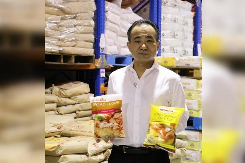 Mr Shuichi Sato, chief executive officer of Phoon Huat, with retail packs of its flour. The company faced a huge demand and found it challenging to pack its 25kg sacks of flour into 1kg packs fast enough.