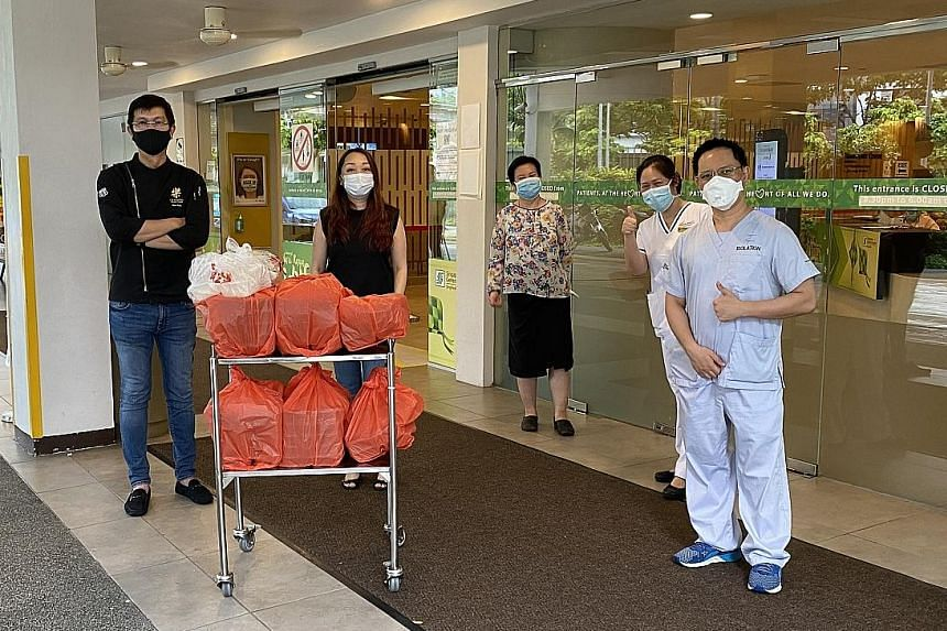 Mr Ben Tan and his wife Catherine Fong (both in black) delivering free bento sets to healthcare staff at Singapore General Hospital. The food (right) is prepared by staff at their modern Chinese fusion restaurant Le Fusion.