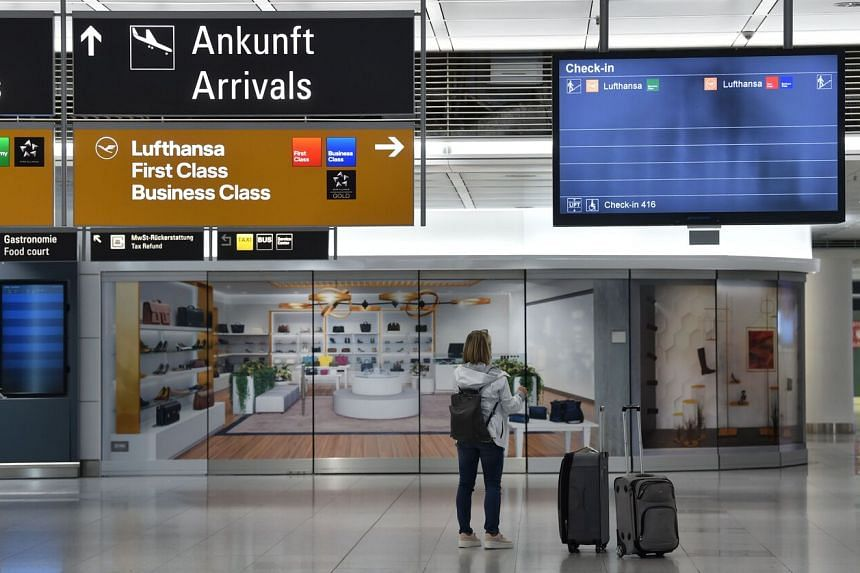 A traveller stands in front of a check-in screen at the Franz-Josef-Strauss airport in Munich, southern Germany, on June 10, 2020.