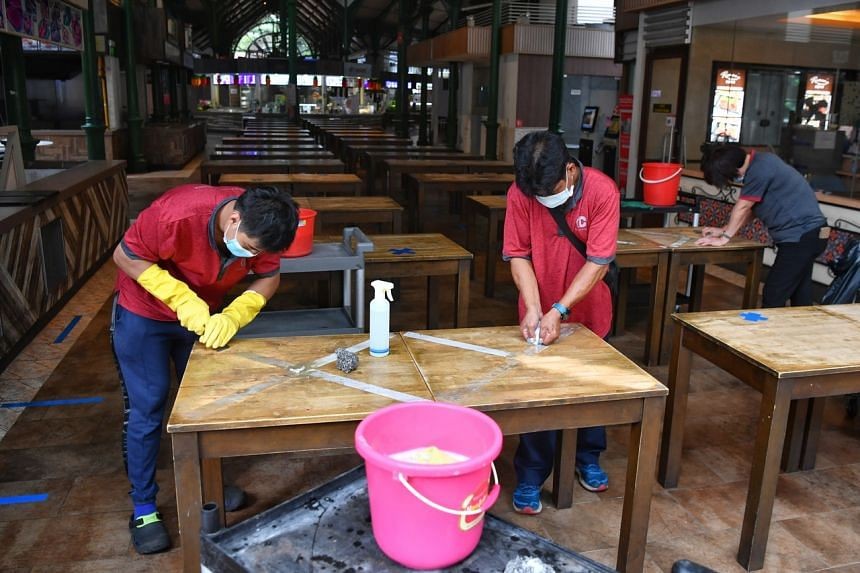 Cleaners removing masking tapes from tables at Lau Pa Sat on June 15, 2020.