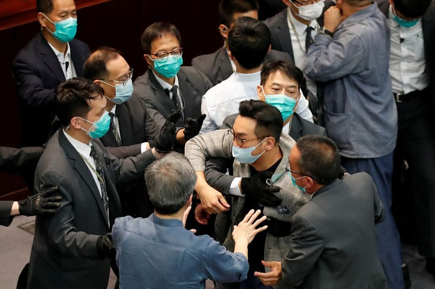 Mr Alvin Yeung (centre) being restrained by security officers at a Legislative Council meeting last month.