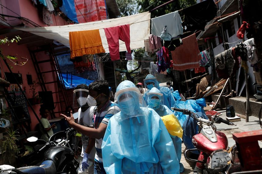 Healthcare workers and volunteers visiting the Dharavi slum in Mumbai earlier this month. The authorities have knocked on 47,500 doors since April to measure temperatures and oxygen levels, and have screened almost 700,000 people, in an aggressive ef