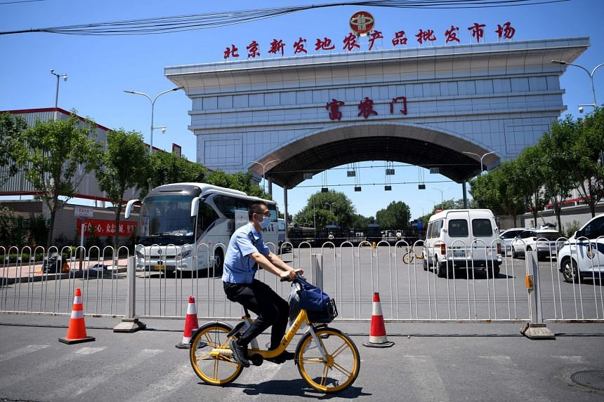 A security officer riding past the closed Xinfadi Wholesale Market in Beijing yesterday. Fengtai, the area where the market is located, has been declared a high-risk area. Those who visited the market on or before May 30 have been asked to voluntaril