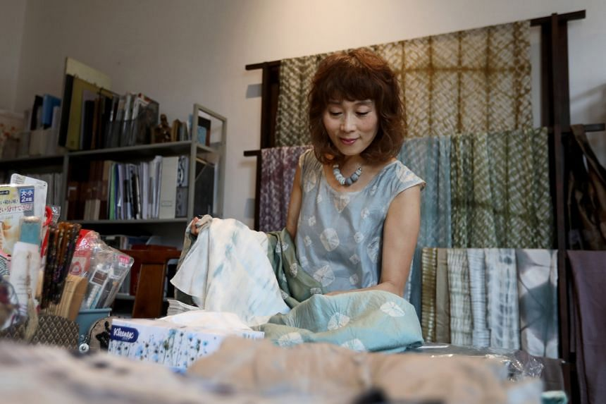 Ms Emiko Nakamura, founder and designer of emgallery, sorting through different fabrics in her home studio while her shop remains shut. She had to store her textiles and other products at home for nearly five months, while waiting for renovations on