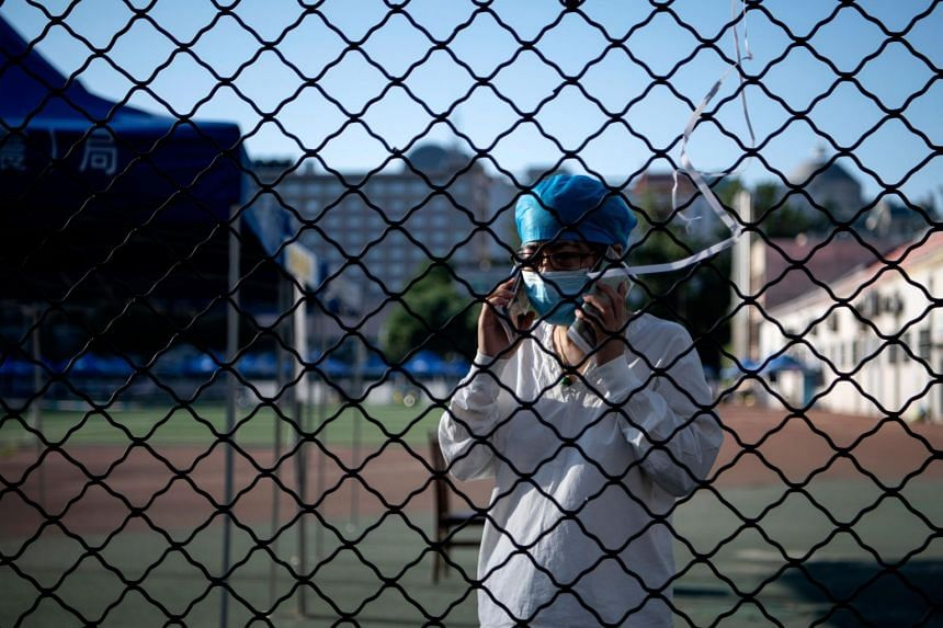 A medical personnel uses her mobile phone at Guang'an Sport Center in Beijing on June 14, 2020.