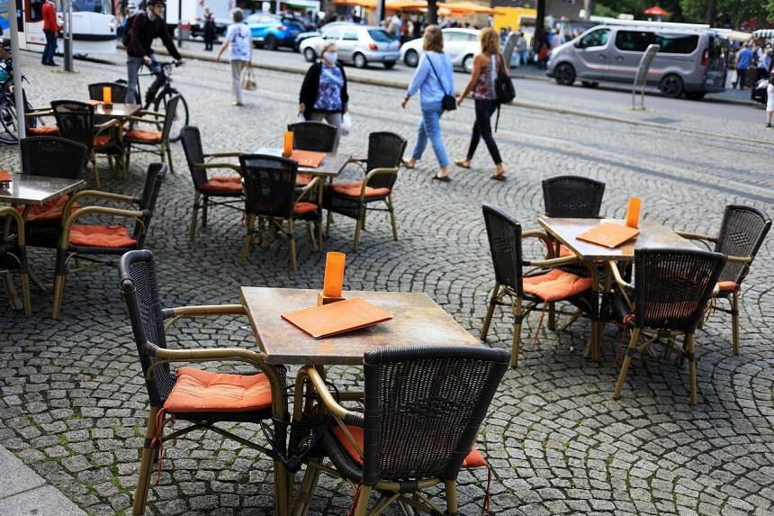 Pedestrians pass empty restaurant tables in the main city square in Erfurt, Germany, on June 12, 2020.