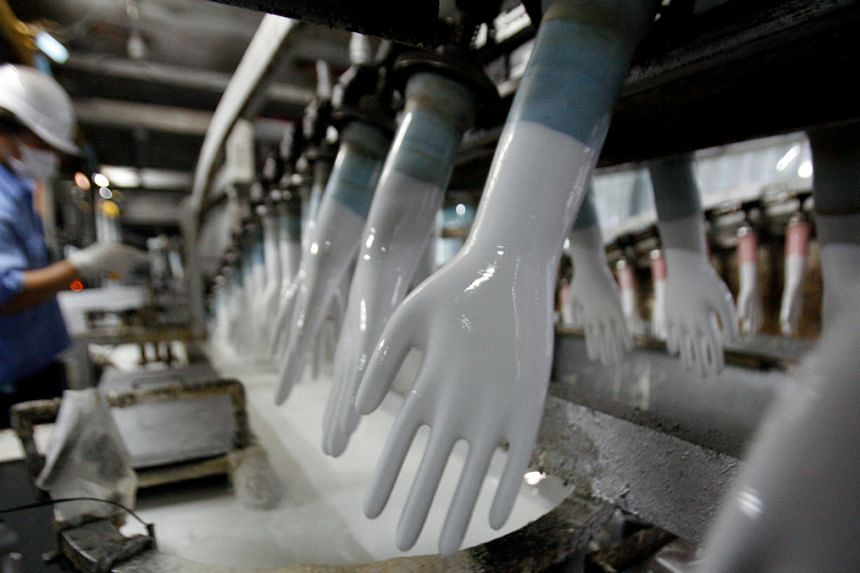 A worker inspects newly-made gloves at Top Glove factory in Klang, Kuala Lumpur, on Jan 13, 2009.