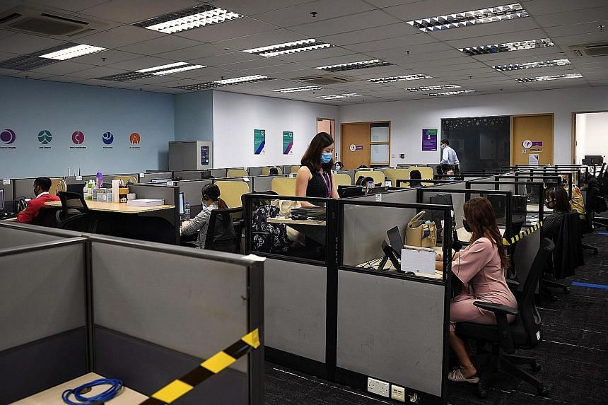 Call centre agents at Enterprise Singapore's call centre in Tai Seng. Trade and Industry Minister Chan Chun Sing said the agents do not just address queries, but also facilitate communication between businesses and government agencies. ST PHOTO: KUA