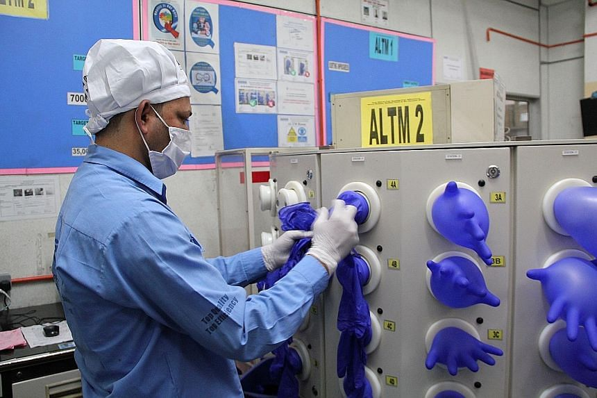 A worker inspecting newly made gloves at a Top Glove factory in Klang, Malaysia, in March. Top Glove Corp, Supermax Corp, Hartalega Holdings and Kossan Rubber Industries have all benefited from a jump in demand for gloves due to the coronavirus pande