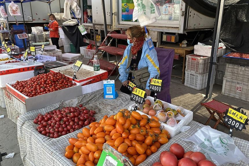 Tomato seller Ma Xiaoli (left) at Beijing's Dayanglu Market yesterday. She was allowed to continue running her stall while awaiting the results of her Covid-19 test. Most vendors at the meat section (right) of the market had packed up ahead of the ma
