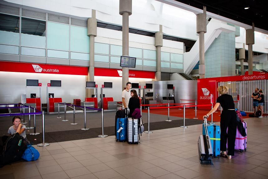 Passengers prepare to check-in at the Virgin Australia counter at Brisbane domestic airport on April 21, 2020.