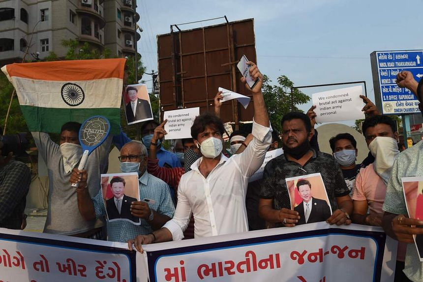 Members of a non-governmental organisation hold placards and shout slogans in Ahmedabad on June 16, 2020.