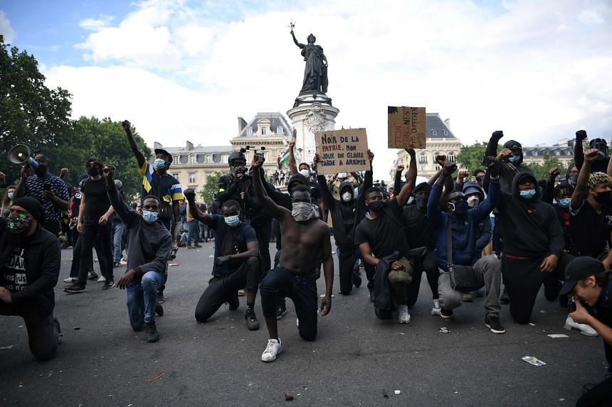 Men take to the knee during a rally on Place de la Republique in Paris, on June 13, 2020.