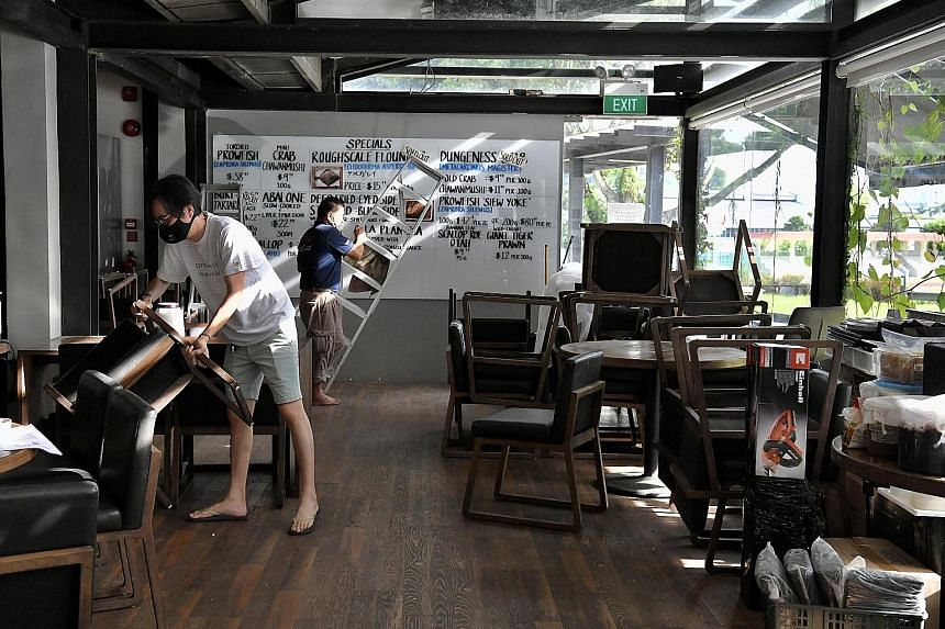Naked Finn owner Tan Ken Loon (left), 45, setting up the tables and chairs in his eight-year-old seafood restaurant at Gillman Barracks yesterday as he got ready for the start of phase two tomorrow, when food and beverage outlets can restart dine-in