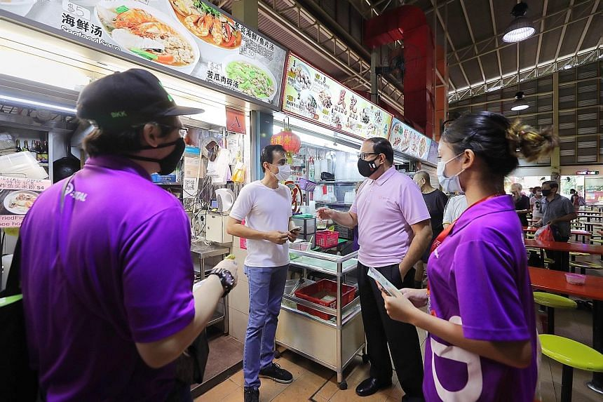 Communications and Information Minister S. Iswaran talking to Kashmir Sliced Fish Soup stall owner Manpal Singh, 45, who recently signed up to offer the SGQR e-payment option, at West Coast Market Place yesterday. With them were SG Digital Office amb