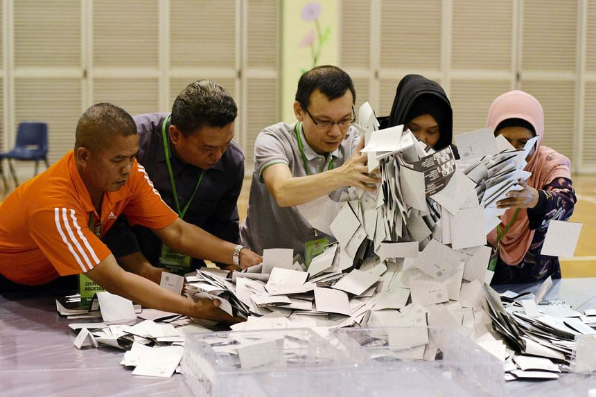 A photo from Sept 11, 2015, showing counting assistants pouring out ballots at Bedok Town Secondary School.