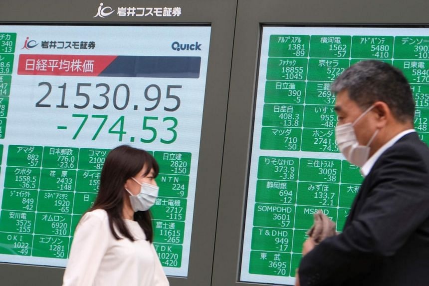 Pedestrians walk past an electronic quotation board in Tokyo on June 16, 2020.