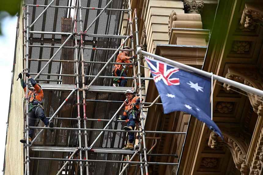 Workers at a construction site in Sydney's central business district yesterday. Australia lost some 227,000 jobs last month, more than twice the 100,000 expected. Separately in New Zealand, bank analysts predict the economy will contract by as much a
