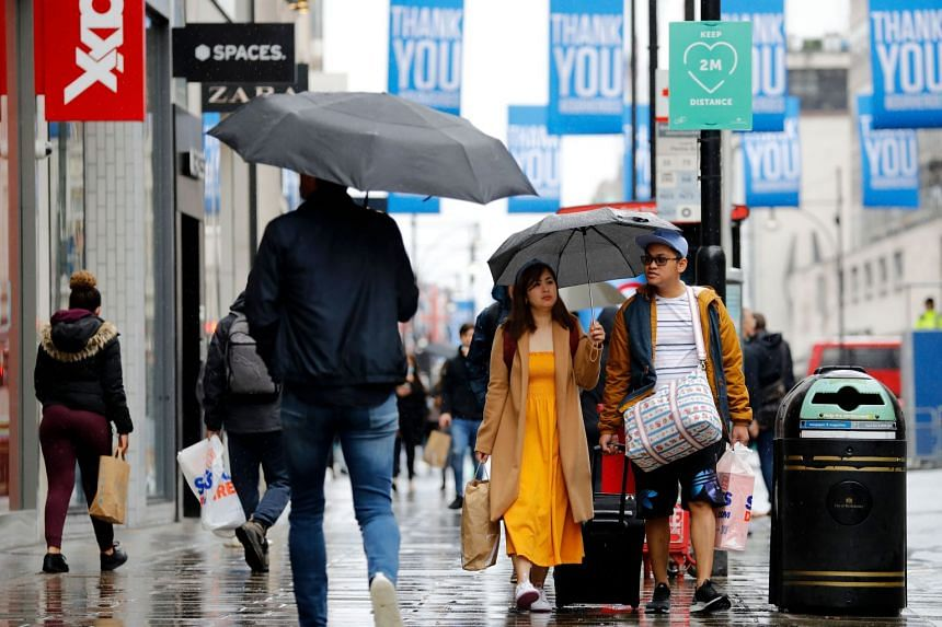 Shoppers shelter under umbrellas on Oxford Street in London on June 18, 2020, as some non-essential retailers reopen.