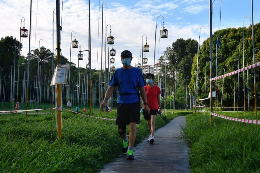 People walking through a field, where Kebun Baru Birdsinging Club members have hung up their cages so that the birds can bask in the sun, on June 19, 2020.