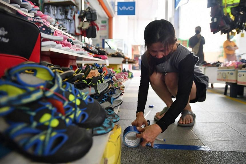 Madam Lim Chin Kim, the boss of I-Smile Shoes, pasting safe distancing markers on the floor at her shop in Tampines on June 19, 2020.