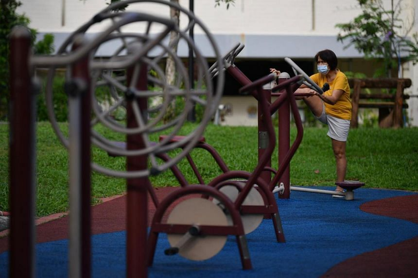 A woman exercises at the fitness corner at Tampines Central Park on June 19, 2020.