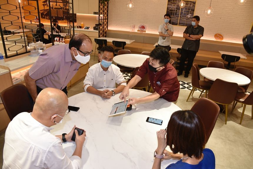 Communications and Information Minister S. Iswaran (left) at White Restaurant's Suntec City outlet on June 19, 2020.