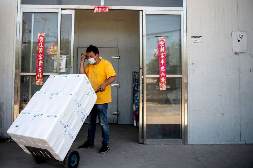 A worker moving produce at the closed Xinfadi market in Beijing. The outbreak last December in Wuhan also started in a market. Above: Chefs waiting to be tested for Covid-19 in Beijing yesterday. Right: Customers buying live seafood at a supermarket